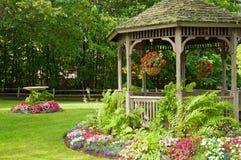 Bloemen en gazebo in park Stock Afbeelding