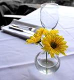 Bloemen en glas op lijst Royalty-vrije Stock Afbeelding