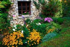Bloemen en stenen-gebouwd huis Stock Foto