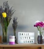 Bloemen en van huisdecoratie de opstelling met levende glimlach en leert berichtraad royalty-vrije stock afbeelding