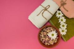 Bloemen in het water en handdoeken op roze achtergrond stock afbeelding
