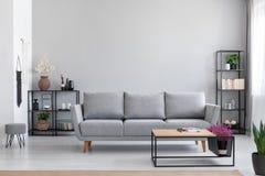 Bloemen in houten lijst voor grijze sofa in modern eenvoudig flatbinnenland met kruk stock fotografie
