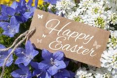 Bloemen met het bruine etiket van de kaartraad en gelukkige Pasen royalty-vrije stock fotografie
