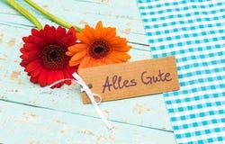 Bloemen met kaart en Duitse teksten, Alles Gute, middelenbeste wensen stock foto's