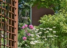 Bloemen, metaaltraliewerk en hangende die mand worden gebruikt om de kant van een rode schuur in Groton, doctorandus in de letter Royalty-vrije Stock Fotografie
