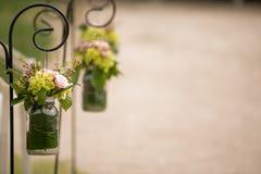 Bloemen in metselaarkruiken bij huwelijksceremonie Stock Foto