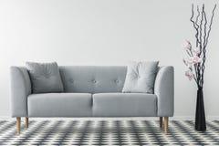 Bloemen naast grijze bank met kussens in minimaal woonkamerbinnenland met gevormde vloer Echte foto stock foto