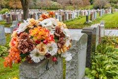 Bloemen op een grafsteen in een begraafplaats met honderden grafstenen Royalty-vrije Stock Foto's