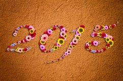 2015 bloemen op feestelijk op Fragment van moderne ruwe gipspleisterrug Royalty-vrije Stock Afbeelding