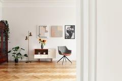 Bloemen op kast tussen gouden lamp en grijze stoel in wit flatbinnenland met installatie Echte foto stock afbeeldingen