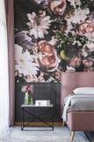 Bloemen op lijst naast roze bed in slaapkamerbinnenland met gevormd behang Echte foto stock fotografie