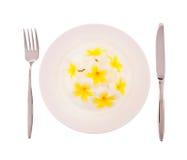 Bloemen op witte plaat met vork en mes Royalty-vrije Stock Afbeeldingen