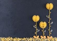 Bloemen uit diverse deegwaren op de donkere leiachtergrond die worden gemaakt, topview Bloemen van deegwaren worden gemaakt die Stock Afbeeldingen