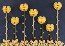 Bloemen uit diverse deegwaren op de donkere leiachtergrond die worden gemaakt, topview Bloemen van deegwaren worden gemaakt die Royalty-vrije Stock Fotografie