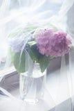 Bloemen in vaas achter het gordijn van Tulle op venster Royalty-vrije Stock Fotografie