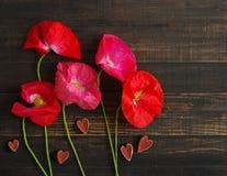 Bloemen van roze wilde papaver en rode houten harten Papaverboeket van bloemen op een oude houten achtergrond Stock Foto