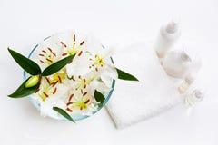 Bloemen van witte lelies in een ronde kom met handdoek stock afbeelding