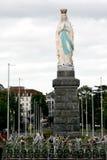 Bloemen voor Maagdelijke Mary in pelgrimsstad Lourdes stock foto's