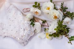 Bloemen witte nam wild en de Gouden bruiloftringen op de witte stof van de parelkleur toe Stock Foto