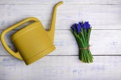 Bloemenboeket met gieter op houten lijst Hoogste mening Stock Afbeelding