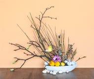 Bloemendecoratie lente-Pasen met Jonge Takjes, Eieren en een Kuiken stock foto's