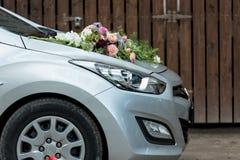 Bloemendecoratie op de grijze bonnet van de huwelijksauto stock foto's