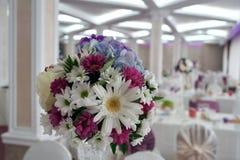 Bloemenregeling in een restaurant Mooi boeket voor huwelijk stock afbeeldingen