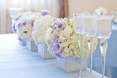 Bloemenregeling met witte en blauwe bloemen en kaarsen Stock Afbeeldingen