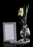 Bloemensamenstelling met een kader en een glas stock afbeelding