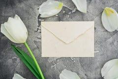 Bloemensamenstelling met witte tulpen en document envelop op donkere achtergrond Vlak leg, hoogste mening Bloemenpatroonachtergro Stock Afbeelding