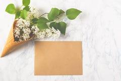 Bloemensamenstelling Sering in wafelkegel en ambachtenvelop op witte marmeren achtergrond Vlak leg, hoogste mening, exemplaarruim Royalty-vrije Stock Afbeeldingen