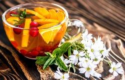 Bloementhee met sinaasappel, Amerikaanse veenbes, munt en ijs Stock Foto