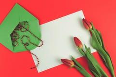 Bloementulpen en groene envelop met witte kaart op rode achtergrond Royalty-vrije Stock Fotografie