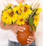 Bloemenzonnebloemen in handen op de witte zomer als achtergrond, een bouque Stock Foto