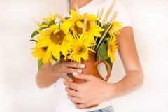 Bloemenzonnebloemen in handen op de witte zomer als achtergrond, een bouque Stock Afbeeldingen