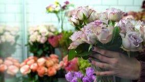 Bloemist die bloemen in de bloemwinkel schikken Het plaatsen van mooie lilac rozen in de voorzijde stock footage