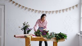 Bloemist die groot en modern boeket van bloemen in document verpakken bij bloemwinkel stock fotografie