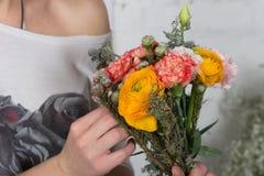 Bloemist die helder oranje en roze boeket maken Royalty-vrije Stock Foto's
