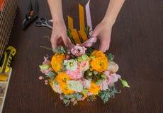Bloemist die helder oranje en roze boeket maken Royalty-vrije Stock Foto