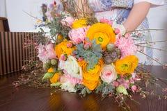 Bloemist die helder oranje en roze boeket maken Stock Afbeelding