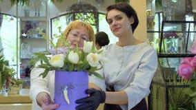 Bloemist en haar hulp demonstarate volledige bloemsamenstelling stock video