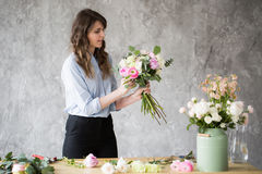 Bloemist op het werk: vrij jonge vrouw die tot manier maken modern boeket van verschillende bloemen Royalty-vrije Stock Foto's