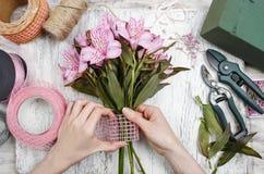 Bloemist op het werk: vrouw die boeket van alstroemeriabloemen schikken Royalty-vrije Stock Afbeelding
