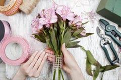 Bloemist op het werk: vrouw die boeket van alstroemeriabloemen schikken Royalty-vrije Stock Foto