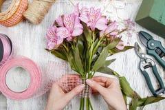 Bloemist op het werk: vrouw die boeket van alstroemeriabloemen schikken Royalty-vrije Stock Foto's