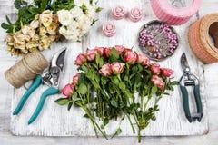 Bloemist op het werk Vrouw die boeket van roze rozen maken stock afbeeldingen