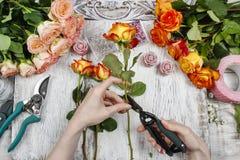Bloemist op het werk Vrouw die huwelijksboeket van oranje rozen maken stock foto