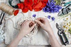 Bloemist op het werk Vrouw die rieten kroon met wilde bloem verfraaien Royalty-vrije Stock Foto's