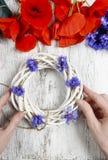 Bloemist op het werk Vrouw die rieten kroon met wilde bloem verfraaien Stock Foto