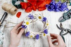 Bloemist op het werk Vrouw die rieten kroon met wilde bloem verfraaien Royalty-vrije Stock Afbeeldingen